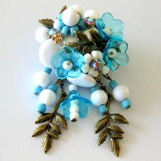 Brooch in the Miriam Haskell Style of Turquoise & White Beads with vintage Swarvski crystal rhinestones and brass findings. Hand wired onto filigree backings.