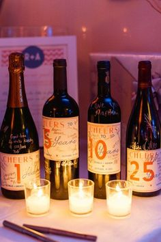 guests sign wine bottle labels for wedding guest book