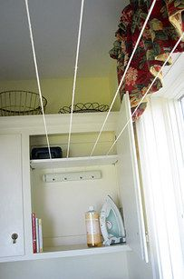 Speaking of line dry: hide retractable clothes lines in a cabinet, then stretch them across to the opposite wall when you need them. | 29 Incredibly Clever Laundry Room Organization Ideas