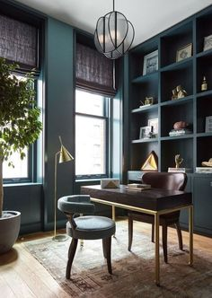 The designers transformed the apartment's third bedroom into a home office with custom built-ins. The walls boast a jade-toned wallcovering from Calico Wallpaper | http://archdigest.com