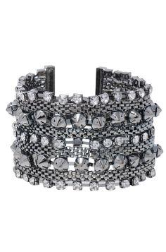 O bracelete grande de spikes é uma peça moderna. Essa bijuteria fina deve ser usada em eventos sofisticados, devido ao seu brilho magnífico. Combine essa pulseira, banhada a prata, com um maxi colar, para um visual noturno.