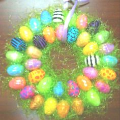 My 1st wreath I made. I used 2 pieces of cardboard, plastic Easter eggs, plastic Easter grass, small piece of ribbon, and a hot glue gun to glue it all..