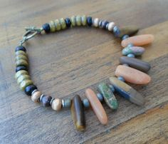 This 7.25 inch long bracelet was handmade in the spirit of Mother Nature with Mixed Matte Stones, including Tiger's Eye and Unakite, framed with wood accents. This piece has also been specially charged with Healing Reiki Energy.