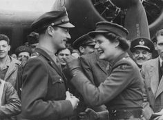 """Lieutenant Mary Churchill cleans Coca-Cola off of Colonel Harry Lebar, commanding officer of the 381st Bomb Group after she christened a B-17 Flying Fortress nicknamed """"Stage Door Canteen"""", 21 April 1944. Mary Churchil, the youngest daughter of the Prime Minister, today christened a U.S. bomber """"Stage Door Canteen"""". She was accompanied by Vivian Leigh, Lawrence Olivier (partly visible on right) and several other well-known screen stars."""
