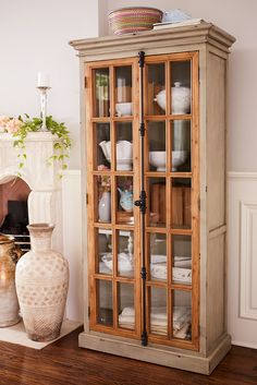 "Originating in 19th century Europe, the ""Cremone bolt"" is a traditional casement-window locking device with a latch/handle mechanism. Featured on all of Pier 1's hand-hewn Cremone cabinetry, it's as beautiful as it is functional. Also featured: Soft gray wood frames with protracted crown molding, contrasting natural wood casements and tempered pane-glass windows."