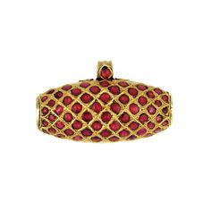 An Antique Gold and Ruby Amulet  Orissa, India  19th Century    A gold barrel amulet inset with cabochon rubies on one side and engraved and worked gold on the reverse.