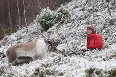 Fiona Smith smiles as she sits with Monty the reindeer in Glenmore where fresh snow fell today