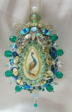 Blue, Green, Gold Peacock Egg Ornament: Vintage cameo, Has pale green silk backdrop. Trimmed with filigree butterfly, ornate braid, green glass beads, & sequins.
