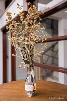 centro de mesa simples e charmoso com garrafinha de vidro, renda, pingente e flores secas. Foto: Gisele Rampazzo