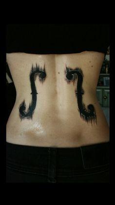 F holes in a violin tattoo on back. Loveeee.
