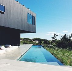 Black monolithic house with infinity pool
