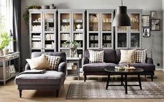 A living room with a grey three-seat sofa, chaise longue and a black round coffee table. Combined with four grey glass-door cabinets.