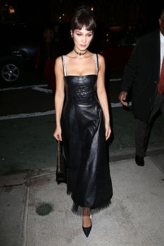 """In a leather Dior Spring 2017 dress with a quilted bustier, """"Christian Dior"""" straps and tulle hemline, pointed-toe pumps, chain strap handbag and jeweled choker while out in New York."""