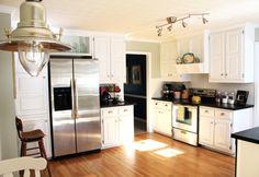 Kitchen.  White cabinets dark countertops.  cabinet next to fridge