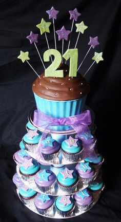 """Blue, Purple and green themed 21st - Giant cupcake tower for a 21st birthday. Not sure if you can see it, but the toppers spell out """"happy birthday caroline"""" I also made the tower itself out of cake boards, coconut cream cans and my trusty hot glue gun :)"""