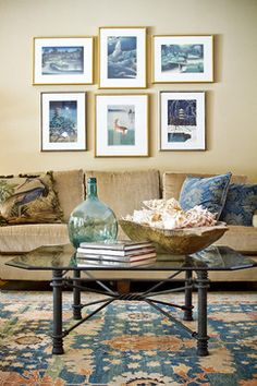 Living room with tan sofa and walls, peacock blue Oriental rug and throw pillows, turquoise glass bottle, and a rustic wood dough trough - by Allison Jaffe Interior Design - photo by Brio Photography