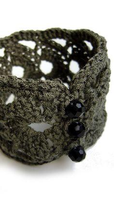 Gehäkeltes Armband in Khaki/Graugrün.  Verschlossen wird es mit drei tiefschwarzen Glasschliffperlen. ** Länge ca. 18,5 cm**  Gehäkelt aus dünnem Bändchengarn von Lana Grossa 25 %...