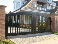If I had the money, I would build a tall iron grate around my property with brick columns every couple of yards along the front drive. And then I'd add a driveway gate such as this one (only iron).