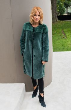 Sienna Miller wears a teal fur coat with skinny jeans and velvet pointed-toe boots