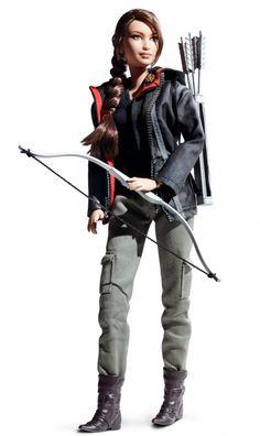 A Mattel criou uma réplica perfeita de Katniss (Jennifer Lawrence), com direito à miniatura do broche de tordo, seu arco e flecha, as botas especiais para florestas, além das grossas e características tranças no cabelo. Linda!