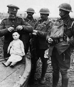 British soldiers play with a porcelain doll left abandoned in an empty village. France, WWI.