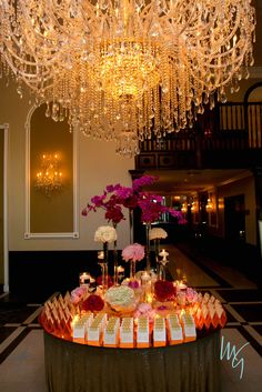 Adam Leffel Productions Escort Card Table. Towers of fuchsia orchids and peony stand tall over clusters of white roses, light pink & red peony, and white hydrangea. They sit on a custom gold mirror table top accompanied by floating candles and monogramed escort cards. #adamleffelproductions #escortcards #entrance #wedding #pink #red #gold #modern #candle