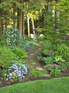 Create your own enchanted forest with low plants that mix well with large and bushy shrubs, all making way for a rustic stepping path.