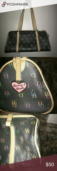 Barrel Dooney & Burke Purse Dooney & Bourke purse with DB print all over on black leather. Straps are tan leather and inside of purse it has light blue lining. Two pockets with zipper inside. Has some minor discoloration on the outside Dooney & Bourke Bags Mini Bags