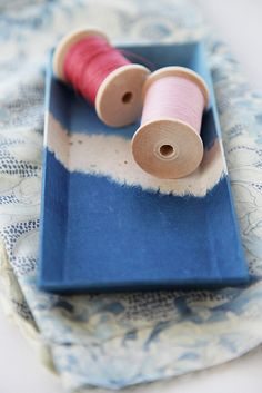 Blue tray with wooden spools