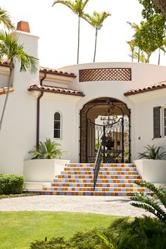 The house features a staircase with risers tiled in alternating colors. An arched entryway fitted with wrought-iron gated in an open pattern, opposite, allows a welcoming glimpse into the courtyard beyond.