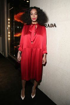 Solange Knowles wears a red silk Prada dress with white pointed-toe pumps