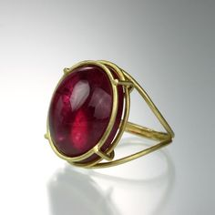 This minimal and sculptural Rosanne Pugliese ring has a recycled 18k yellow gold 'Cage' setting that perfectly showcases the raspberry colored tourmaline. This unique cabochon ring with a bright pop of color is just what your jewelry box has been missing!Size 6.