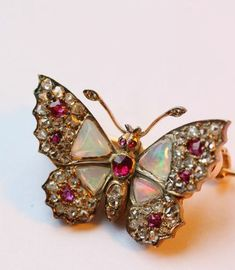 ~Gold gem set brooch in the shape of a butterfly, in silver pavé set with rose cut diamonds, cushion cut rubies in the wings, and thorax and cabochon cut opal highlights to the wings, France, circa 1870~