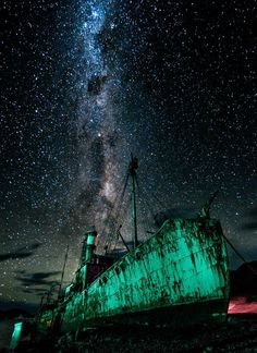The Petrel, an abandoned whaling and sealing ship, sits beached on the shore at Grytviken, South Georgia beneath the Antarctic night sky. The green and red lights illuminating the ship are from the port buoys in Grytviken Bay. A replica of the James Caird, the small lifeboat Ernest Shackleton used to sail from Elephant Island to South Georgia in one of the greatest sailing adventures in history, is moored to the bow of Last Voyage of the Petrel Photo by Eric Lew — National Geographic Your…
