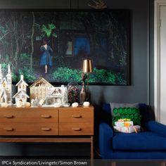 Ein märchenhaftes Ambiente schafft dieses Gemälde in Kombination mit der außergewöhnlichen Dekoration auf der Holzkommode. Der royalblaue Retrosessel lädt zum…