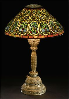 "A RARE ""BLACK-EYED SUSAN"" TABLE LAMP  Estimate: 250,000 - 350,000 USD   with a ""Tree Trunk"" base    leaded glass and patinated bronze    circa 1910, Image: Sotheby's"