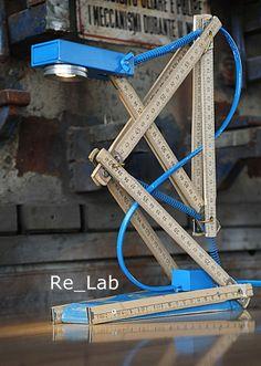 Metra è una lampada di design industriale creata da un metro in legno, usato, opportunamente piegato e fissato su una base in legno di abete colorato. Metra ha come fonte di illuminazione un mini faretto led bianco caldo da 3w. Ideale come regalo per Lui e Lei. Il colore è personalizzabile. Dimensioni L x P x H : 22 x 9 x 33 cm.