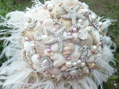 a mixture of shell and star fish shaped broaches with shells, probably not the feathers Seashell Bouquet, Beaded Bouquet, Beach Wedding Bouquets, Beach Weddings, Bridal Bouquets, Shells And Sand, Burlap Ribbon, Pearl Brooch, Vintage Rhinestone