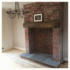 Exposed brick fireplace with indian stone hearth and reclaimed wooden lintel