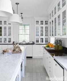 """Island houses need clean white kitchens,"" says Lindroth. She painted walls and cabinets White Dove in Aura and the ceiling Decorators White in Waterborne Ceiling, both by Benjamin Moore. Pendant fixtures, Visual Comfort.   - HouseBeautiful.com"