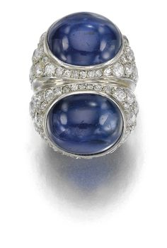 JEWELS FROM THE PERSONAL COLLECTION OF SUZANNE BELPERRON Of double corps design, set with two sapphires cut en cabochon, single-, circular- and brilliant-cut diamonds, size 43, French assay marks  SAPPHIRE AND DIAMOND RING, CIRCA 1945