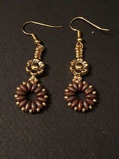 These handcrafted earrings are perfect to wear any occasion. Materials: - Brown Picasso super duo beads - gold seed beads - gold flower - gold hook Measure: - 2 1/2 inch