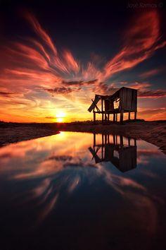 Photo : Une maison abandoné devant un lac au moment d'un couché de soleil