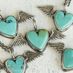 Turquoise Heart Necklace with Wings by ThirtySixTen on Etsy. Sterling silver wings hold these tiny, genuine turquoise heart shaped stones.
