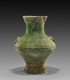 """Chinese Han Dynasty, small green glazed pottery storage jar (hu): the shoulder flanked by a pair of moulded mask and faux ring handles, covered in a bright green glaze with some areas of silvery iridescence; H: 13 """"; Provenance: J. T. Tai & Co., Inc., New York; The Arthur M. Sackler Collections, New York, March 1, 1970; Else Sackler, New York, By Descent"""