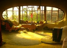 Looking out a cob home into a greenhouse extension... Very earthship...