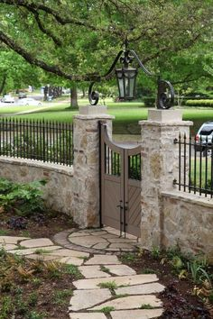Beautiful stone wall, fencing and curved gate.