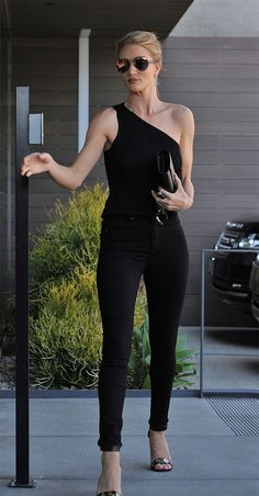 Rosie Huntington-Whiteley usa look total black com blusa de um ombro só e calça skinny.
