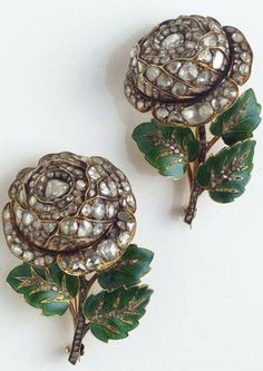A pair of diamond, enamel and gold brooches the matched brooches of rose motif, the 14k gold flower tops set throughout with rose and table-cut diamonds, completed by a 14k gold stem with 18k gold leaves, decorated with green enamel, accented by table-cut diamonds.