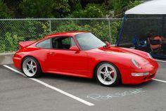 Guards red Porsche 993 Carrera 4S with duckbill on Techart wheels.